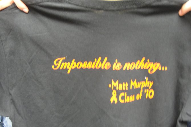 """The F-M boys' basketball team had t-shirts made up to benefit former manager Matt Murphy, who passed away last year. The back reads """"Impossible is Nothing,"""" a slogan Murphy used often."""