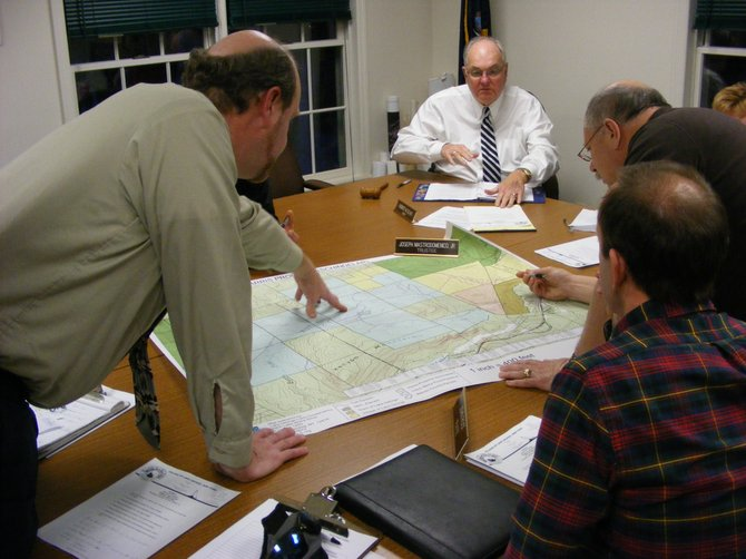 At their special meeting held Jan. 19, Lake George Village Board members and village Public Works Superintendent Dave Harrington (left front) locate on a map a plot of land near the Berry Pond Tract that the Lake George Land Conservancy offered to sell the municipality. Village leaders passed on the opportunity.