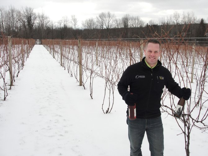 Owera Vineyards Director of Operations Ben Reilley holds two of the winery's most popular products, a bottle of Cazenovia Blush and semi-dry Riesling, Jan. 20 at Owera's location in Cazenovia.