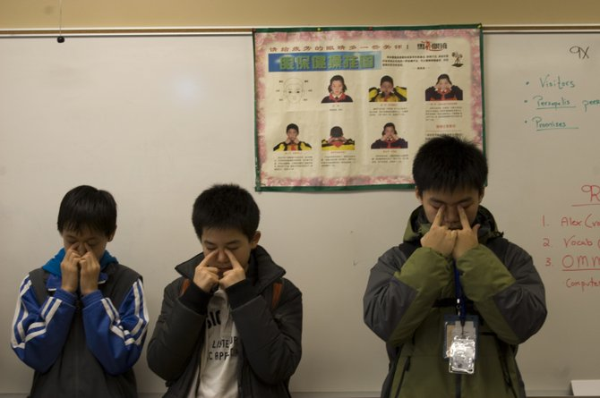 Three Chinese students show a Social Studies class in Guilderland High School how to  morning eye exercises to relieve stress.