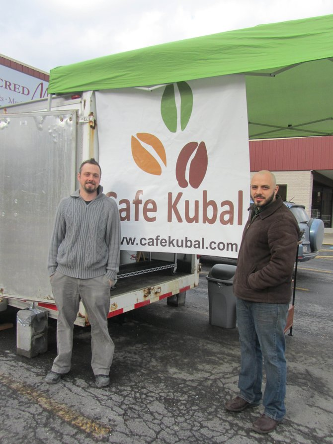 Cafe Kubal owner Matt Godard, left, and general manager Chris Deferio stand outside a trailer, from which coffee is being served this week. Godard hopes to have the Eastwood location reopen on Monday after a week of renovations.