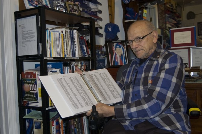 Frank Massey, an 82-year-old Scotia resident, holds his binder detailing all of the New York Giants player signatures he has collected. The binder is broken down into various categories, such as player number and college attended.