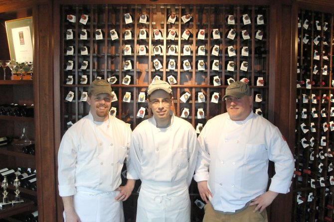 Brewster Inn Executive Sous Chef Stephen Franks, left, stands with executive chef Jason Wright and sous chef Dave France in front of one of the Brewster Inn's wine racks. The three chefs were named the best in Syracuse after winning the first annual Iron Fork competition on Jan. 29.