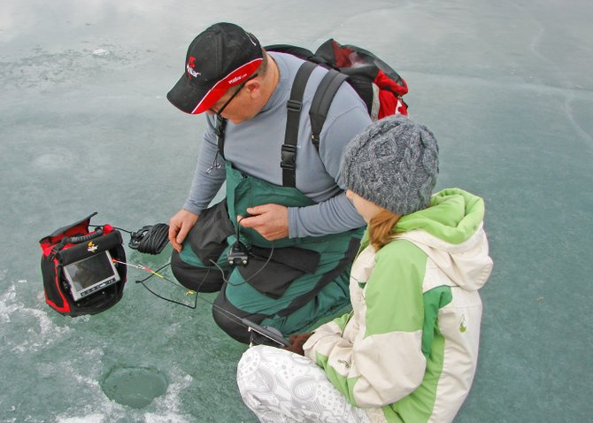 Shawn Hayes, a professional fisherman, teaches Alyssa Tucker about ice fishing during a program for Ticonderoga Middle School students.