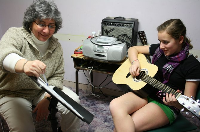 Mary Salvatore works with a student at Brown School during a guitar lesson.