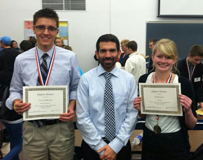 Scotia-Glenville High School students Corey McKenna, left, and Sarah Dean, right, stand with science research teacher Chris Judd, center, after receiving honors for their projects at the Eastern Regional Junior Science and Humanities Symposium.