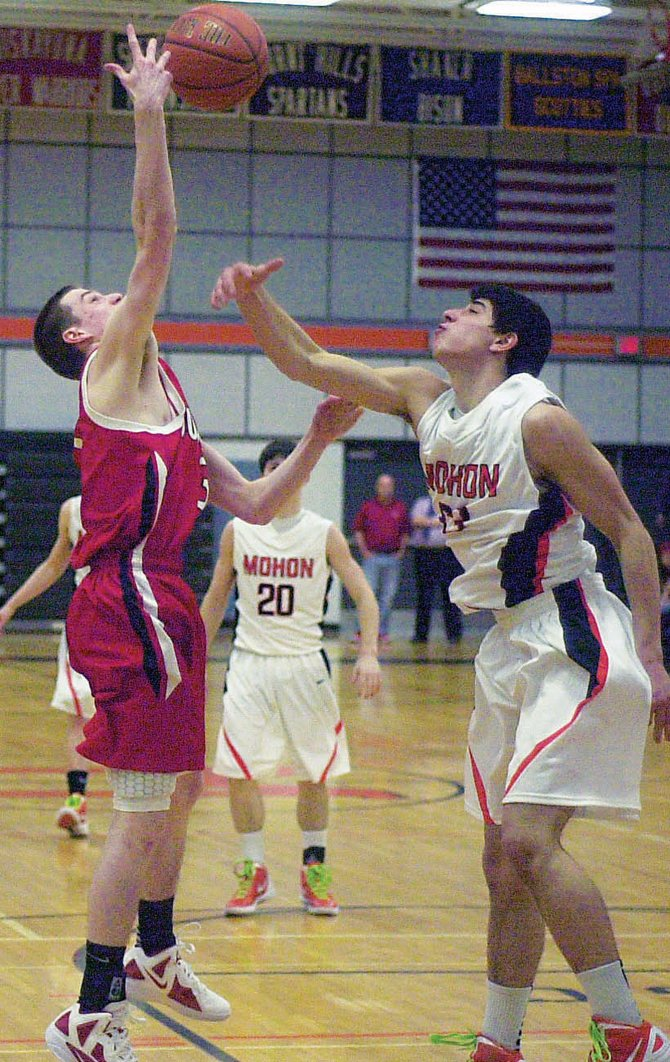 Mohonasen's Billy Manikas, right, loses out on a rebound to Guilderland's `Brian Crupi during Tuesday's Suburban Council South Division game.