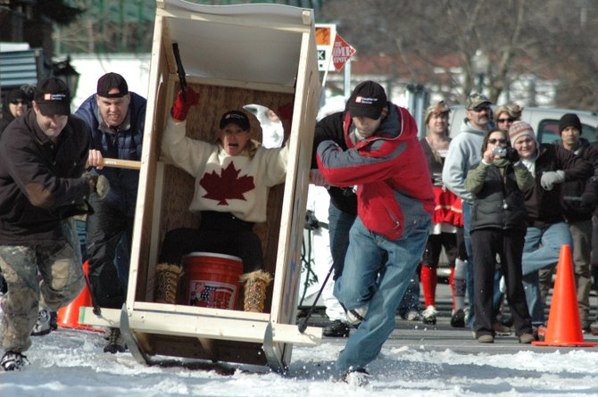 HOLD ON!  A team of competitors in the Lake George Winter Carnival outhouse race  Saturday lurch off the starting line, giving their rider a reason to reach for the handrails. This team, digging in to drag their custom-built craft  toward a finish line, represented Home Depot of Queensbury. The race, an annual favorite, drew a robust crowd as well as a videographer for a national cable channel.