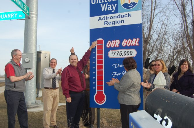 Jerry Morrow places the final fundraising tag outside the United Way offices in Plattsburgh, announcing that the organization met its 2012 fundraising goal.
