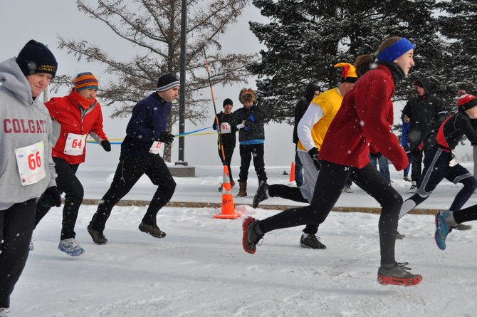 Participants in the United States Snowshoe Association qualifying 5k race begin their trek in front of the Highland Forest Skyline lodge on Feb. 12 as Cazenovia resident and event organizer Chary Griffin, center, wearing a Russian ushanka hat, starts her timer. Racers had planned on competing in the 5k and 10k jaunts using snowshoes, but were allowed to wear running shoes due to lack of snow. Cazenovia High School student Rae Tobey, 18, won the 10k race and will compete in the USSSA National Championship, to be held Feb. 25 in Frisco, Colo.