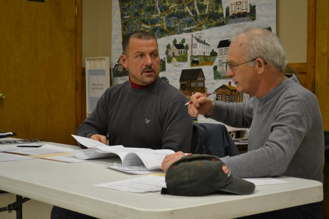 Altona Board Member Joey Snide and Highway Superintendent Fred Therrian  pore over State Highway plans to figure out what Route 11 sidewalks might need maintenance at the Feb. 13 meeting.