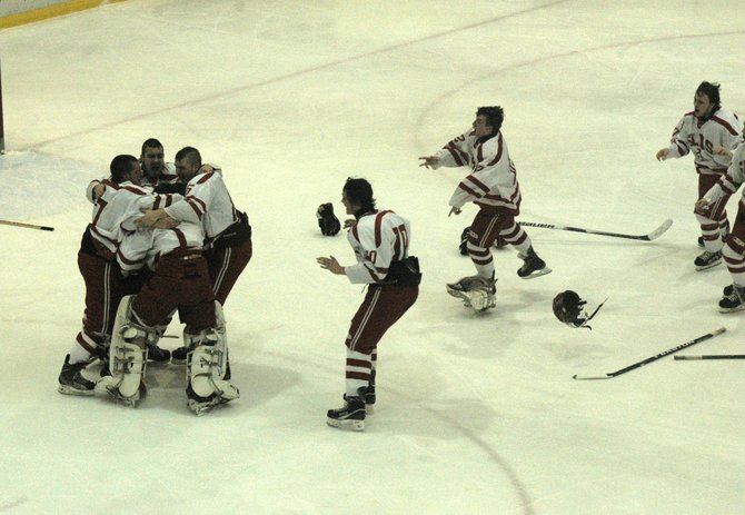 Members of the Saranac Lake hockey team mob goalie Blake Darrah to celebrate their second straight Section VII title Feb. 27.