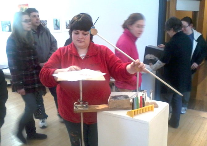 """Amanda Brezicky, a Cazenovia College junior majoring in studio art, demonstrates her drawing machine,""""Twinelliptic Pendulum,"""" at the 2012 Student Juried Exhibition in the Art Gallery of Reisman Hall on Feb. 20."""