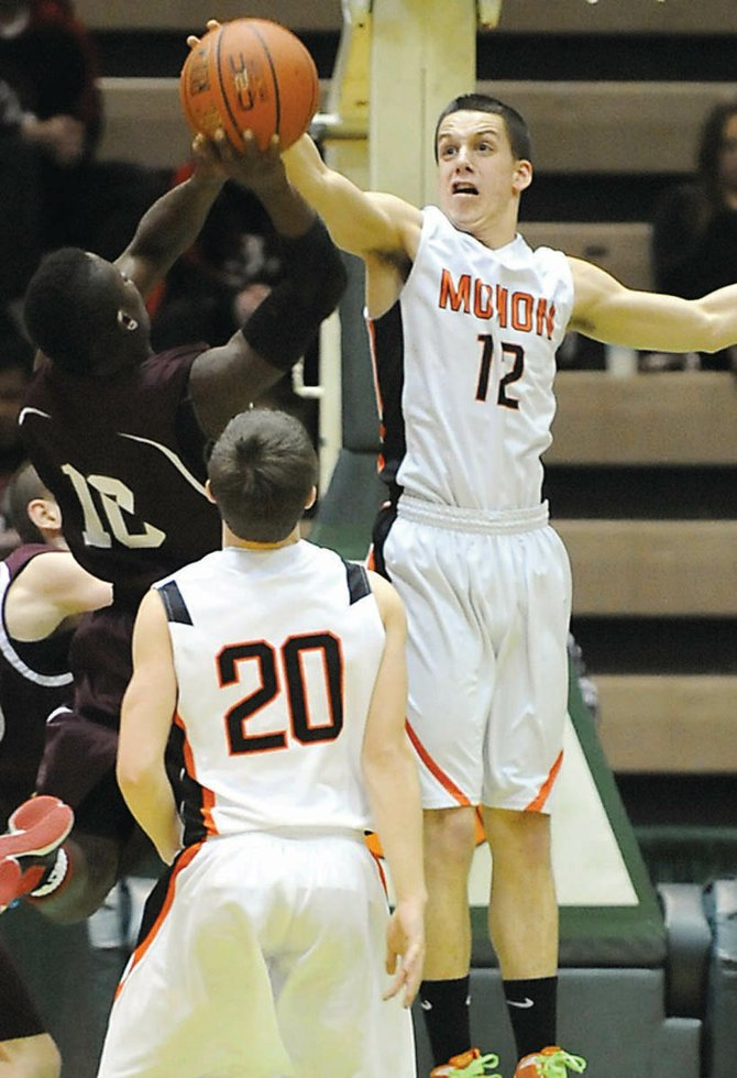 Mohonasens Killian Tallman blocks Raheem Felders shot during Sundays Section II Class A quarterfinal game against Lansingburgh at Hudson Valley Community College.