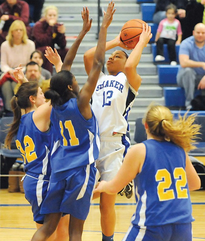 Shakers Madison Rowland takes a shot while guarded by two Bishop Maginn players during last Fridays Section II Class AA playoff game. 