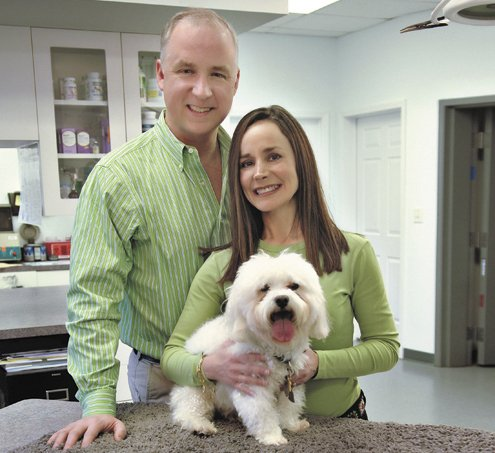 Matt and Jamie Mulcahy, founders of the Shamrock Animal Fund, stand alongside their rescue dog, Bentley, inside the Rockacres Veterinary Hospital in Manlius.