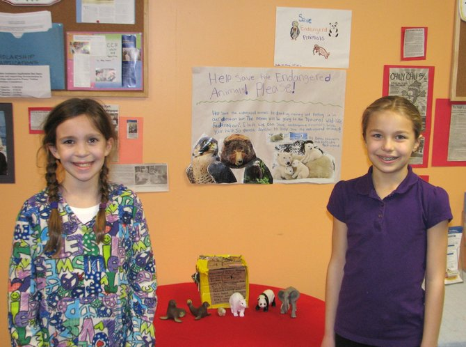 Cassidy Rockwood, left, and Betsy Chanatry stand in front of their donation box at Cazenovia Children's House. The girls are looking to raise money for a donation to the National Wildlife Federation, which protects wildlife and their habitats, in efforts to restore and maintain healthy ecosystems.