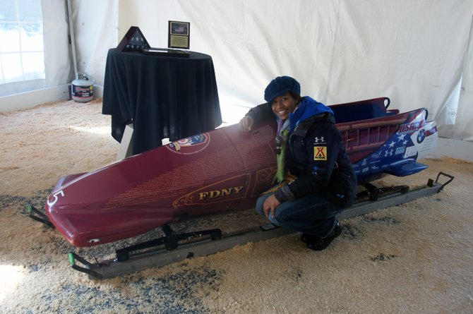Jazmine Fenlator kneels next to the USA-3 sled, dedicated to members of the Fire Department of New York.