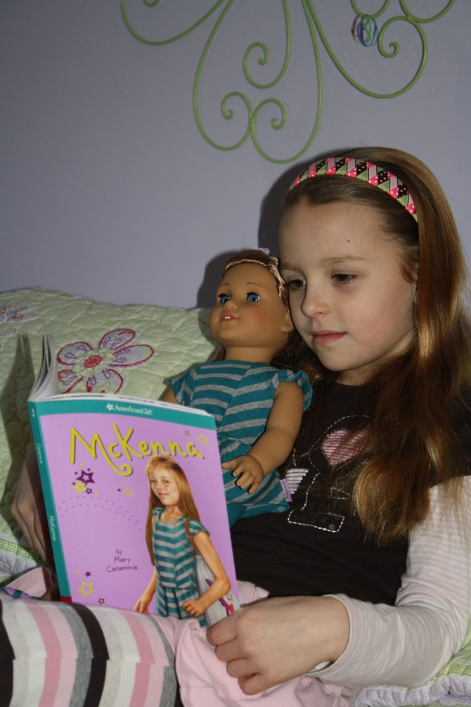 Avery Daggett,8, reads with the McKenna doll. Daggett will also be walking the runway as Marie Grace.