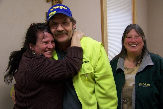 Tanya Wemett hugs her husband Jeff soon after recalling in detail how he suffered a massive heart attack in October, and the fast action of North Warren Emergency Squad personnel — and her son — saved his life. Observing the hug is Laura Eklund (right), who was behind the wheel of the ambulance that drove Jeff to Glens Falls Hospital.