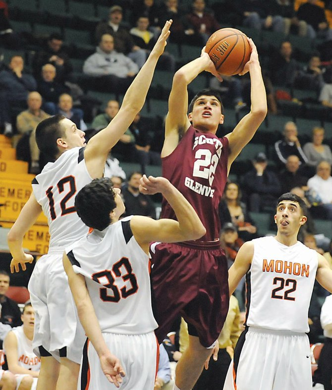 Scotia-Glenville's Chris Zanta (red jersey) shoots in front of Mohonasen's Killian Tallman (12) and Billy Manikas (33) during last Friday's Section II Class A semifinal game at the Glens Falls Civic Center. The Tartans edged the Mighty Warriors 62-61 in overtime.