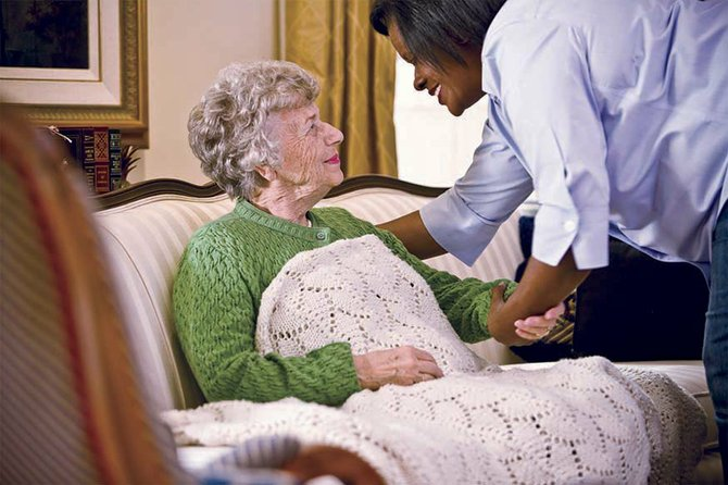 A Home Instead Senior Care aide, right, assists one of her client's.