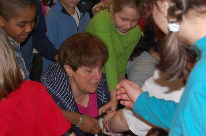 Oak Street Elementary School students gather around Adirondack Humane Society Manager Lil Cassidy for a chance to pet one of the cats she brought in.