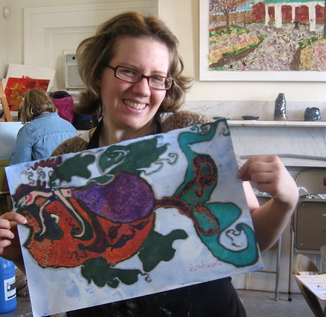 "Sarah Baker at the art studio of Creative Endeavors showing her painting, ""The Mermaid and the Fish""."
