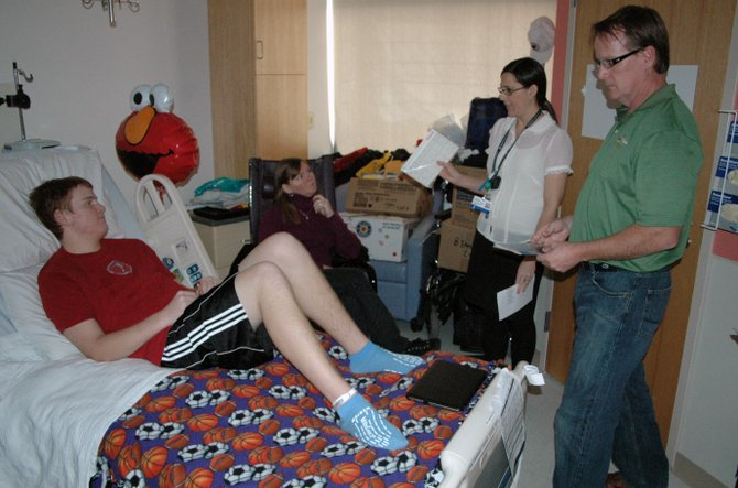 "Connor Marvin sits on his hospital bed while Jennifer Gilande, center, talks with he and his parents, Darlene Mitchell (left of Gilande) and Walter ""Smitty"" Marvin, III, about the medicine that the 16-year old now has to take."