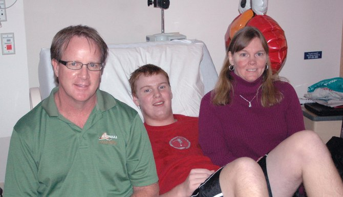 "Connor Marvin, center, with parents Walter ""Smitty"" Marvin and Darlene Mitchell."