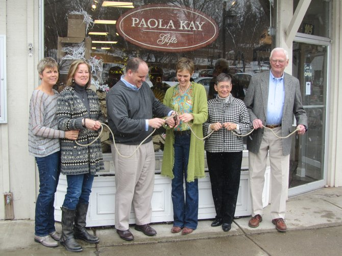 From left to right: Eileen Helmer, JoAnn Purcell, Fayetteville Mayor Mark Olson and shop owner Wendy Lee and her parents, Lynne and Jack Reading, cut the rope during the grand opening of Paola Kay on March 10.