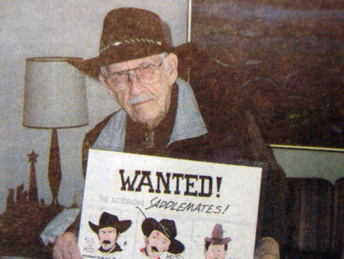 "Sid Couchey, in 2003, with cartoons of the three ""bad guys,"" featured in a comic book about local western star Tom Tyler. Couchey passed away Sunday, March 11."
