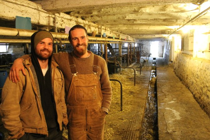 Greyrock Farm Owner Matt Volz, left, and Tim Biello, manager of vegetables and horses, stand in front of the milking area at the farm in Cazenovia. Volz began his business in 2010 with just one full-time employee. He now has five other workers helping with the daily routine and harvesting raw milk.