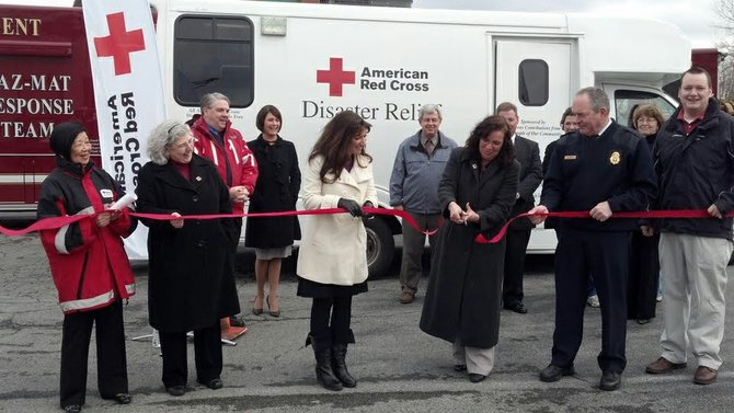 "Chairman of the Board for the American Red Cross of Central New York Dot Hall, right center, cuts the ribbon at the Syracuse Fire and Rescue Training Center in Syracuse on March 2. With Hall stand Fire Chief Mark McLees, Tiffany Latino from Senator DeFrancisco's office, and Red Cross Emergency Services volunteers. Before cutting the ribbon, Hall accepted a certificate of ""congratulations and best wishes"" from the CenterState Chamber of Commerce Ambassadors for successfully completing the two-year $90,000 DRV Campaign."