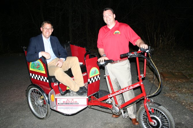 Steve Tomb (left) and Mike Smith, proprietors of the Adirondack Pedal Cab Co., pose in one of their their bicycle-powered rickshaws soon after presenting details Monday March 19 of their proposed service to the Lake George Village Board. The two plan to have 10 to 20 of their pedalcabs circulating in Lake George as soon as this summer, transporting tourists to various destinations in exchange for donations.