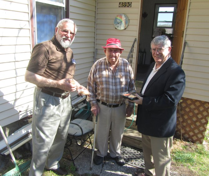 20-year ECHO volunteer Bruce Widger, left, of Marcellus, and Marcellus Mayor John Curtin, far right, stand with George Schmidt, 94, outside his home on Kasson Road in Camillus after delivering him a hot meal at lunchtime.