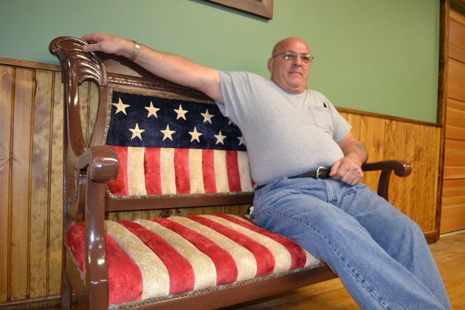 Former town supervisor Jim McNeil reclines on the contentious couch in Ellenburg's town hall.