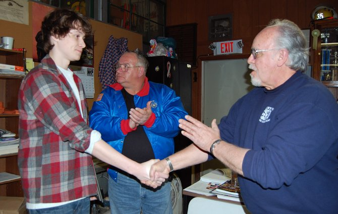 Westport Fire Department members James Westover and Ernie LaPine congratulate Alex Steele during their monthly meeting.