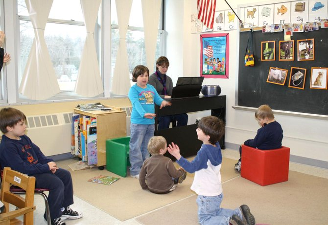 Burton Street Elementary School students Jacob, Emily, Luke, Connor and Elijah listen and as Norma Fowler plays a tune on the electronic piano recently donated by the BSPTA.