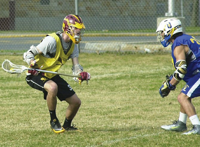 Colonie's Mike Metzger, left, looks for a way around a Queensbury defender during last Friday's scrimmage. Metzger is one of three returning midfielders for the Garnet Raiders this season.