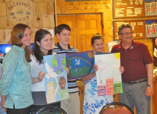 The Schroon Lake Lions Club recently held its annual Peace Poster contest. From left are: Brie Roscrans, Schroon Lake Central School art teacher, Lindsay Palmer, honorable mention, Joseph Foote, winner, Ashley McCoy, honorable mention, and Dennis D'Amico, poster contest chairman.