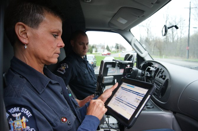 Kelly Glynn, a WAVES volunteer and Camillus resident, fills out the rest of a patient's information with Glenn Randall, a WAVES paramedic and Manlius resident. The iPad has helped make their work much more proficient and efficient, they said.