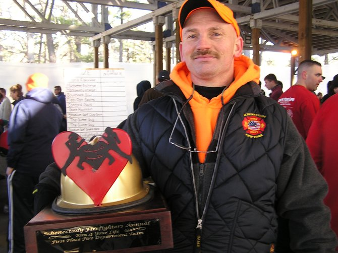 Schenectady Firefighter Lt. Brian Demarest holds the Fireman's Trophy, which any team of runners from an area fire department can take back with them if they are the top firefighter team finishers in the Run 4 Your Life race. Demarest started the race the race to raise awareness to heart health issues amongst firefighters.