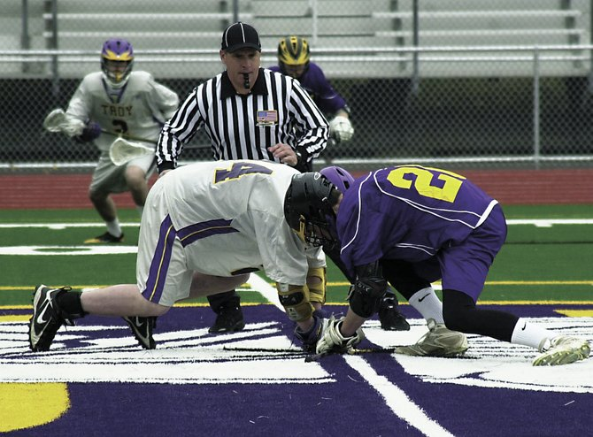 Voorheesville's Nick Jasinski, right, takes the first faceoff for the Voorheesville varsity boys lacrosse team in last Saturday's non-league game against Troy.