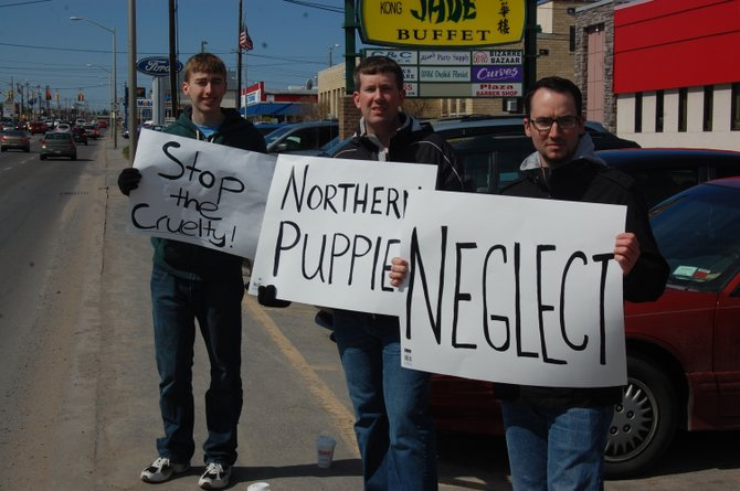 Front, from left to right, Bradley Cech, Terry Cech and Damian Battinelli protest along Route 3 in Plattsburgh.