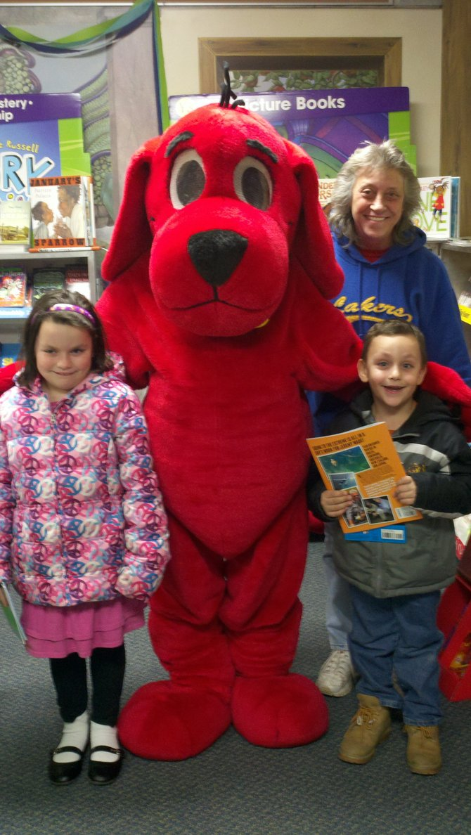 Kindergartner Arizona Petrick, left, poses with her younger brother, grandmother and Clifford (Paige Horan) during the Burton Street Spring Book Fair.