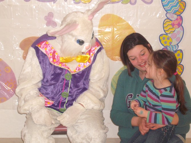 Tehya Holbrook, 3, of Jordan, held by her mother Jen, meets the Easter Bunny.
