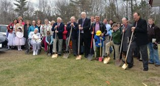 Members of the congregation hold a ceremonial ground breaking ceremony on April 8.