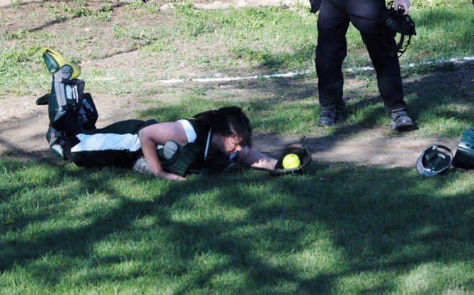 Jennifer McGinn makes a diving catch behind the plate.