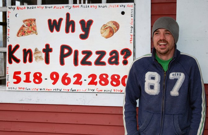 Kevin Simpson stands in front of the newly opened Why Knot Pizza on Main Street in Westport. 